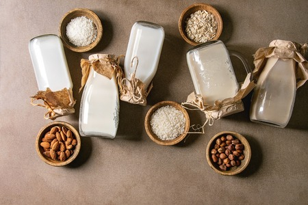 Variety of non-dairy vegan lactose free nuts and grain milk almond, hazelnut, coconut, rice, oat in glass bottles in row with ingredients above over brown texture background. Flat lay, space Stok Fotoğraf - 123293517