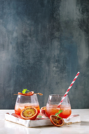 Blood orange iced cocktails in glasses, decorated by slice of oranges and fresh mint, served with retro straw in ceramic tray on white marble table with blue wall at background.