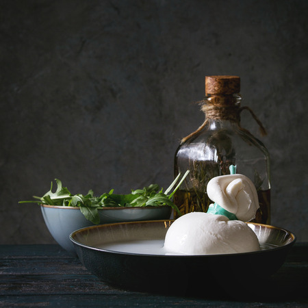 Bowl with whole tied Italian cheese burrata in brine, arugula salad and bottle of olive oil on wooden plank table. Dark rustic style. Square image