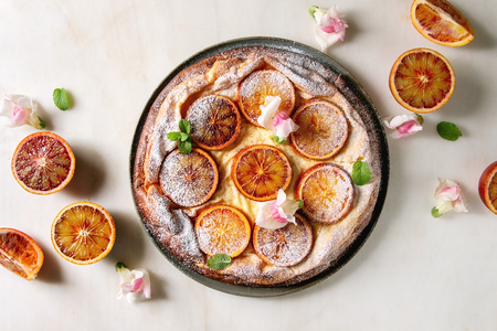 Homemade Cheesecake with sicilian blood oranges, decorated by edible flowers, mint leaves and sugar powder served in plate with cutted oranges above over white marble background. Flat lay, space