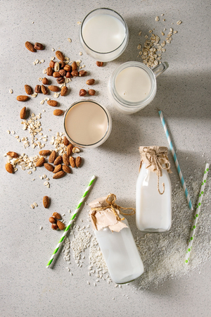 Variety of non-dairy vegan lactose free nuts and grain milk almond, hazelnut, coconut, rice, oat in glass bottles with straws and ingredients above over white spotted background. Flat lay, space