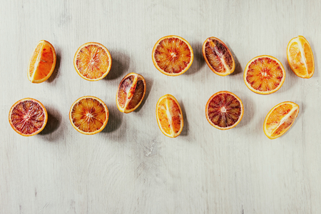 Group of fresh organic Sicilian blood oranges sliced and whole in row over white wooden background. Flat lay, space Imagens