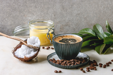 Bulletproof coffee. Keto diet coffee in blue ceramic cup with organic ghee butter and coconut cold press oil in spoons with beans and green branch on white marble table. Grey wall at background.