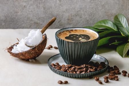 Café a prueba de balas. Café de dieta ceto en taza de cerámica azul con aceite de coco orgánico prensado en frío en cucharas con frijoles y rama verde sobre mesa de mármol blanco. Pared gris en el fondo.