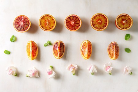Group of fresh organic Sicilian blood oranges sliced and whole, edible flowers, mint leaves in row over white marble background. Flat lay, space Stock Photo