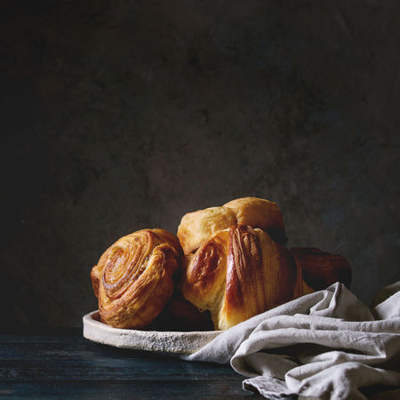 Variety of homemade puff pastry buns cinnamon rolls and croissant in ceramic plate on wooden table. Dark still life. Copy space. Square image Фото со стока
