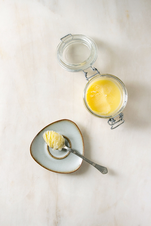 Homemade Melted ghee clarified butter in open glass jar and spoon on saucer over white marble background. Flat lay, space Stock Photo