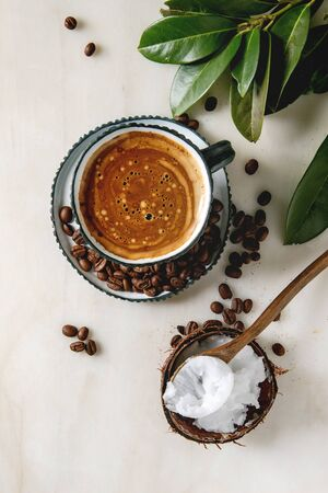 Bulletproof coffee. Keto diet coffee in blue ceramic cup with organic coconut cold press oil in wooden spoon with beans and green branch over white marble background. Flat lay, space