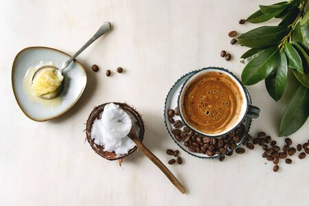 Bulletproof coffee. Keto diet coffee in blue ceramic cup with organic ghee butter and coconut cold press oil in spoons with beans and green branch over white marble background. Flat lay, space 版權商用圖片 - 125293315