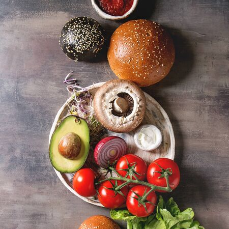 Ingredients for cooking homemade vegan hamburgers. Cheese, avocado portobello mushroom, tomato green sprouts, black and white buns, salad, onion. Dark background. Top view, space. Square image Reklamní fotografie