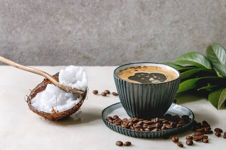 Bulletproof coffee. Keto diet coffee in blue ceramic cup with organic coconut cold press oil in spoons with beans and green branch on white marble table. Grey wall at background. Stockfoto