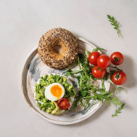 Vegetarian whole grain bagel sandwich with chopped avocado, cream cheese, sun dried tomatoes, egg, arugula served on ceramic plate over white marble background. Flat lay, space. Square image Zdjęcie Seryjne
