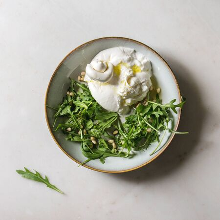 Sliced Italian burrata cheese, fresh arugula salad, pine nuts and olive oil in white ceramic plate over white marble background. Flat lay, space. Square image