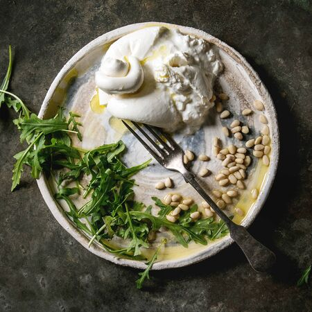 Sliced Italian burrata cheese, fresh arugula salad, pine nuts and olive oil in white ceramic plate over dark metal background. Flat lay, space. Square image