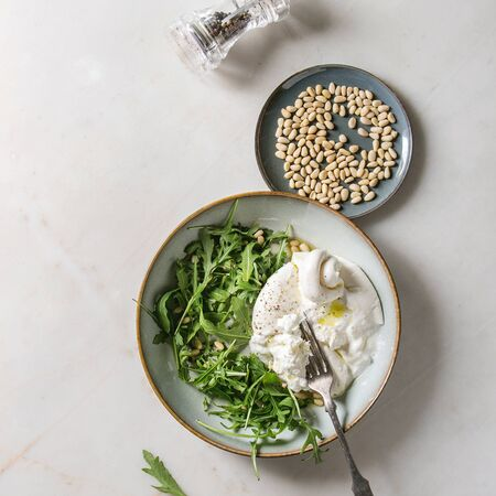 Sliced Italian burrata cheese, black pepper mill, fresh arugula salad, pine nuts and olive oil in white ceramic plate over white marble background. Flat lay, space. Square image 版權商用圖片