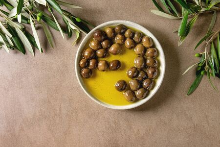 Green whole olives in olive oil served in ceramic bowl with young olive wood branches over brown texture background. Flat lay, copy space