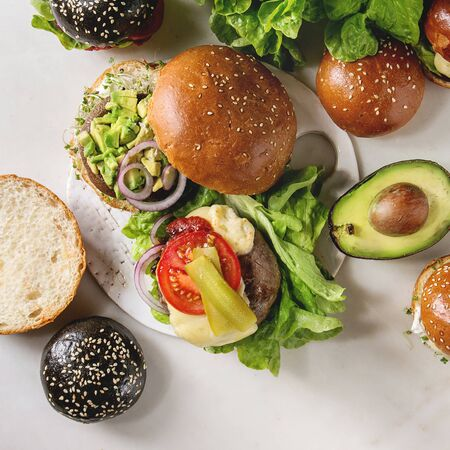 Variety of homemade classic, vegan and mini burgers in wheat and black buns with beef and veal cutlets, portobello mushroom, avocado, melted cheese and vegetables on white marble table. Square image