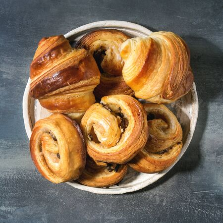 Variety of homemade puff pastry buns cinnamon rolls and croissant served in ceramic plate over blue texture background. Flat lay, space. Square image