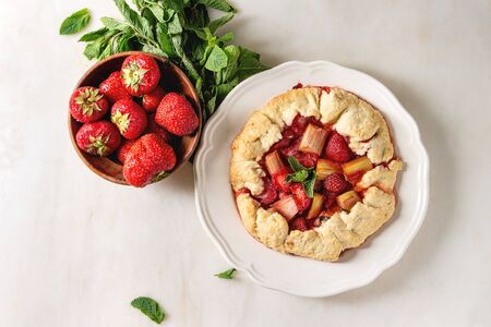Home baking summer berry biscuit pie with strawberry and rhubarb, served in plate with fresh strawberries and mint over white marble background. Flat lay, space