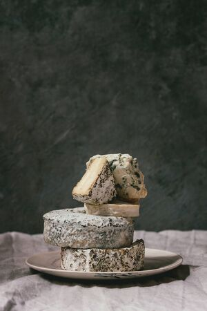 Variety of french blue cheese in stack on plate with flowing honey on grey linen table cloth. Stock Photo