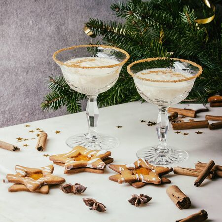 Eggnog Christmas milk cocktail, served in two vintage crystal glasses with shortbread star shape sugar cookies, cinnamon sticks, fir branch over white marble table. Square image
