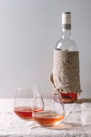 Two glasses of different rose wine standing on grey linen table cloth with bottle. Copy space Stock Photo