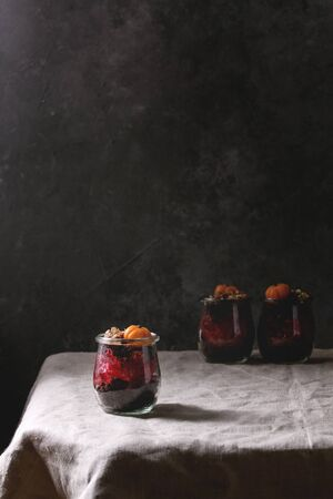 Layered Halloween dessert chocolate biscuit, raspberry jelly, nuts, marzipan pumpkin in glass jars served on linen table cloth with decorative pumpkins. Dark mood.