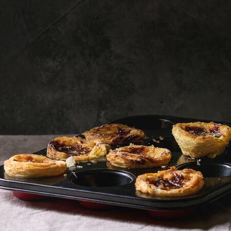 Traditional Portuguese egg tart dessert Pasteis Pastel de nata in black baking tray standing on linen table cloth near dark grey wall. Square image