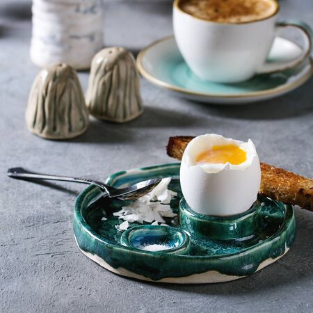 Breakfast with cup of coffee and soft boiled egg, served in green ceramic egg cup with salt, pepper and toasted bread, jug of cream over grey blue table. Square image Archivio Fotografico - 126822374
