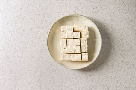 Cutting cubes of tofu, traditional japanese soy cheese in ceramic plate over grey spotted background. Flat lay, space Stock Photo