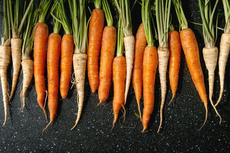 Young carrot and parsnip with tops in row over black texture background. Flat lay, space. Cooking concept, food background.