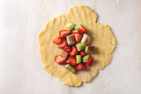 Process of baking summer berry biscuit pie. Rolled shortbread dough, cutting strawberry and rhubarb over white marble background. Flat lay, space
