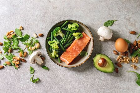 Ketogenic diet ingredients for cooking dinner. Raw salmon, avocado, broccoli, bean, olives, nuts mushrooms, eggs in ceramic bowls. Grey texture background. Flat lay, space Stock Photo