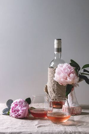 Two glasses of different rose wine standing on grey linen table cloth with bottle and pink peonies flowers. Romantic greeting card. Copy space Stock Photo