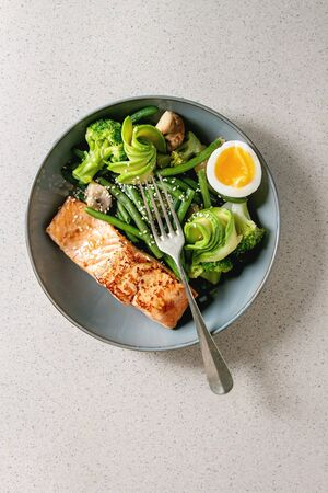 Ketogenic low carb diet dinner grilled salmon, avocado, broccoli, green bean and soft boiled egg in ceramic bowl with fork over grey spotted background. Flat lay, space Stock Photo