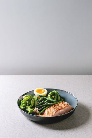 Ketogenic low carb diet dinner grilled salmon, avocado, broccoli, green bean and soft boiled egg in ceramic bowl on grey table. Copy space Stock Photo