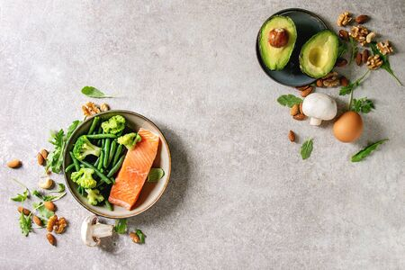 Ketogenic diet ingredients for cooking dinner. Raw salmon, avocado, broccoli, bean, olives, nuts, mushrooms and eggs in ceramic bowls. Grey texture background. Flat lay, space Stock Photo