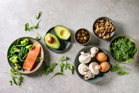 Ketogenic diet ingredients for cooking dinner. Raw salmon, avocado, broccoli, bean, olives, nuts mushrooms, eggs in ceramic bowls. Grey texture background. Flat lay, space