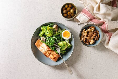 Ketogenic low carb diet dinner grilled salmon, avocado, broccoli, green bean and soft boiled egg in ceramic bowl served with olives and nuts over grey spotted background. Flat lay, space Stock Photo