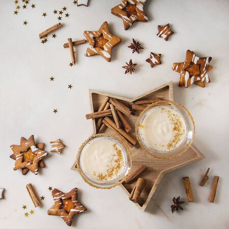 Eggnog Christmas milk cocktail, served in two vintage crystal glasses on wooden tray with shortbread star shape sugar cookies, cinnamon sticks over white marble background. Flat lay, space. Square image