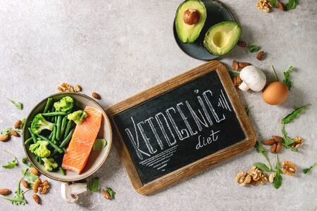 Ketogenic diet ingredients for cooking dinner. Raw salmon, avocado, broccoli, bean, olives, nuts, mushrooms, eggs in ceramic bowls with chalk board lettering. Grey texture background. Flat lay, space Stock Photo