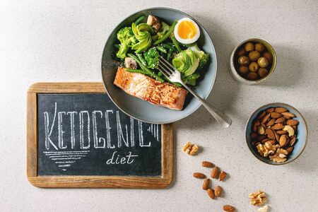 Ketogenic low carb diet dinner grilled salmon, avocado, broccoli, green bean and boiled egg in bowl served with olives, nuts and chalk board lettering over grey spotted background. Flat lay, space
