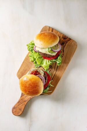 Two homemade fast food burgers classic hamburger or cheeseburger with beef, salad, cheese and tomato served on wooden cutting board on white marble background. Flat lay, space