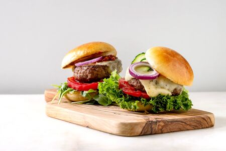 Two homemade fast food burgers classic hamburger or cheeseburger with beef, salad, cheese and tomato served on wooden cutting board on white marble kitchen table. Copy space. Фото со стока