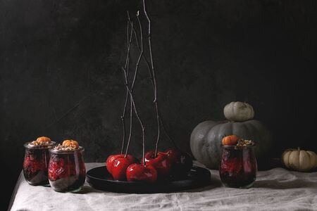 Layered Halloween dessert chocolate biscuit, raspberry jelly, nuts, marzipan pumpkin in glass jars and red caramel apples on branches served on linen table cloth with decorative pumpkins. Dark mood.