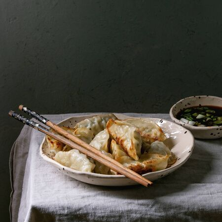 Fried asian dumplings Gyozas potstickers in white ceramic plate served with chopsticks and bowl of soy onion sauce over linen table cloth. Asian dinner. Square image