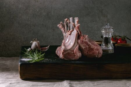 Raw uncooked rack of lamb on wooden cutting board with salt, herbs rosemary, pepper and garlic on grey table cloth as background. Dark still life Stock Photo