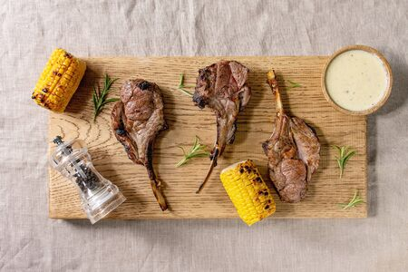 Grilled bbq rack of lamb with sweet corn cobs, rosemary and cheese sauce on wooden cutting board on linen cloth background. Flat lay, space