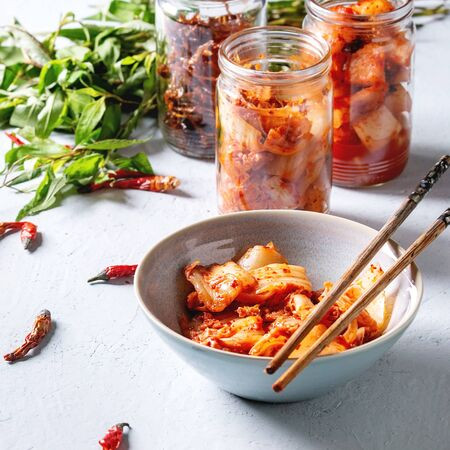 Korean traditional fermented appetizer kimchi cabbage and radish salad, hot spicy anchovies fish snack served in glass jars and bowl with Vietnamese oregano and chili peppers over grey blue table. Squ 스톡 콘텐츠