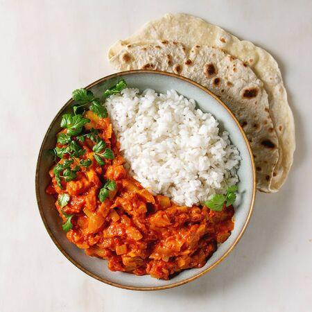 Vegan vegetarian curry with ripe yellow jackfruit served in ceramic bowl with rice, coriander and homemade flatbread flapjack over white marble background. Flat lay, space. Square image Stock Photo